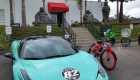 Red Phantom Shadow electric bike next to blue Lamborghini with Buddha statue in the background