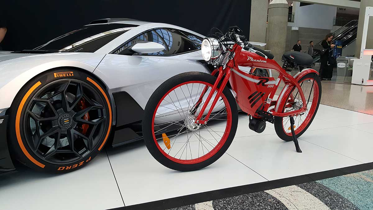 White Lamborghini Aventador Beside Red Phantom R Electric Bike